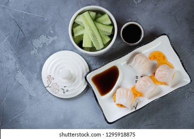 Steamed prawn hargows with cucumber and dipping sauces, flatlay on a grey concrete background, horizontal shot