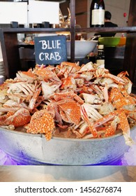 Steamed red blue crabs cut in half in bucket on ice with sign - seafood buffet line