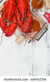 Steamed red lobsters with ginger, spices and seafood utensils on the white rustic wooden table. Maine lobsters. Two boiled lobsters.