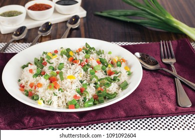 steamed rice with beans, carrot, red capsicum, green capsicum, yellow capsicum, onion, peas, salt, green and red sauce are placed on purple napkin with wooden background.