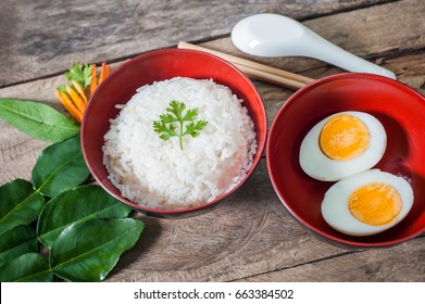 Steamed rice and boiled eggs put in cups and chopsticks with spoon put on wooden boards.