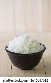 Steamed rice, jasmine rice Thailand genuine rice varieties.Rice in ceramic bowl on a black background blur.image Vertical