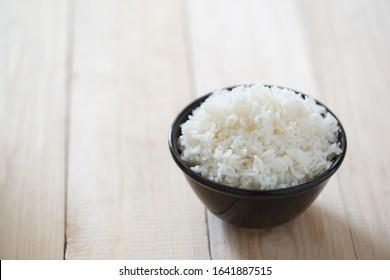 Steamed rice, jasmine rice Thailand genuine rice varieties.Rice in ceramic bowl on a black background blur.