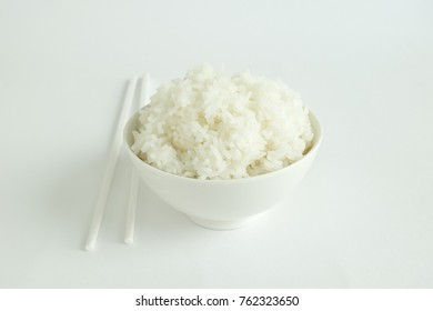 Steamed rice in a white bowl served with white chopsticks on a white background.