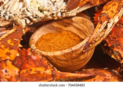 Steamed, seasoned, male jumbo Chesapeake Bay blue claw crabs with claws around a wood bowl of spicy seasoning