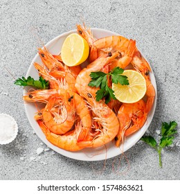 Steamed shrimps with lemon and herbs. Seafood, shellfish. Shrimps prawns on plate.