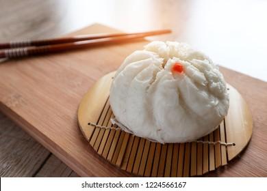 Steamed stuff bun pork with chopsticks on wooden board background, Natural lights photo, Foods concept.
