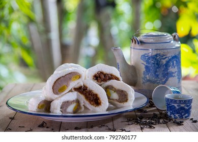 Steamed stuff bun (sa la pao) Stuffed with pork chops and yolks, taro and lotus seeds are placed on a plate and tea pot in garden on wooden table. Chinese food dim sum. Still Life image