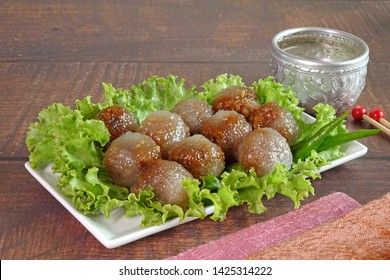 """Steamed tapioca (Sago) balls with pork and peanut filling, the Famous traditional Thai appetizer / street food name """"Saku Sai Moo, served with vegetables and chili. Sago Pearl or tapioca Pearl. Space"""