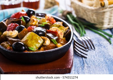 Steamed vegetables with olives and nuts. Selective focus.