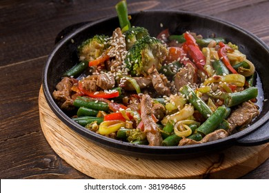 Steamed Vegetables Potatoes, Carrots, Corn, Green Beans, Onion with meat. wooden background