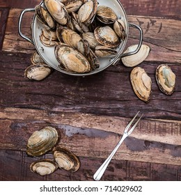 Steamer clams from New England in a whiten colander on a rustic table ready are cleaned and ready for cooking.