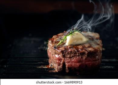 A steaming beef tenderloin steak is grilled in a grill pan with the text copy space. The concept of the recipe , filet Mignon