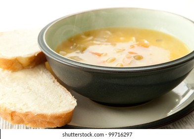 a steaming bowl of chicken noodle soup with fresh slices of sourdough bread thickly buttered on the side. the ultimate comfort food and cold remedy