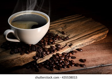 Steaming coffee cup and coffee beans on wood background with copy-space and dark tone.