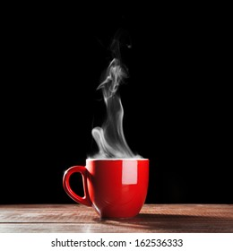 Steaming coffee cup on dark background