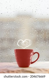 Steaming coffee cup on a rainy day window background with heart shape