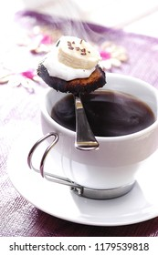 steaming coffee in a white porcelain cup, a small cookie with cream and banana topping on the spoon, close up
