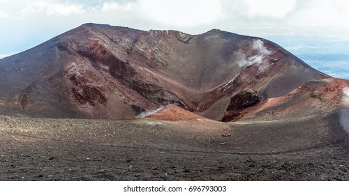 A steaming crater with iron deposits at the summit of Mount Etna, Sicily in summer