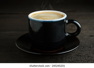 Steaming cup of coffee on wood close-up