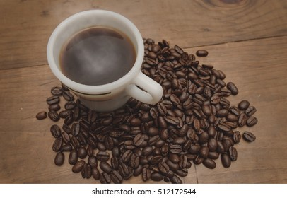 Steaming Cup of Coffee Surrounded by Coffee Beans