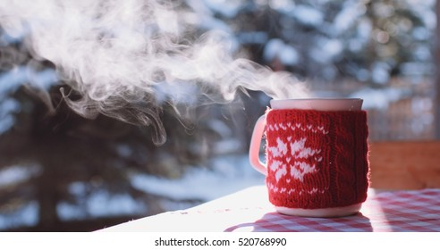 Steaming Cup of Hot Coffee or Tea standing on the Outdoor Table in Snowy Winter Morning. Cozy Festive Red Mug in knitted wear with a Warm Drink in Winter Garden. Christmas Morning Concept