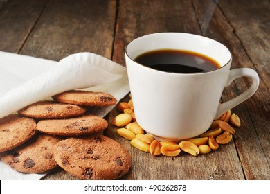 steaming hot coffee, with chocolate cookies and peanuts on rustic wood table