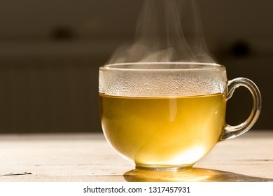 Steaming hot tea in glass mug on a wooden table. Refreshing morning image with a tea cup in back lighting.