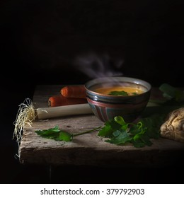 steaming hot vegetable soup with parsley garnish in a clay bowl and ingredients on an old rustic wooden table against a dark background with generous copy space, selected focus