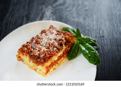 steaming lasagne alla bolognese - dish with hands