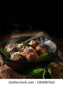 Steaming organic meat balls in tomato sauce, Soffritto Passata, with grated parmesan cheese and bay leaves shot against a dark background with accommodation for copy space.