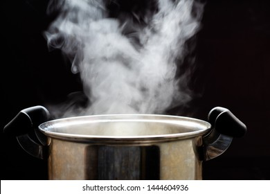Steaming pot on black background. Smoke above boiling soup pot.,hot food and healthy meal concept