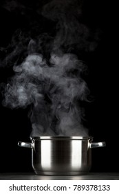 Steaming pot on black background