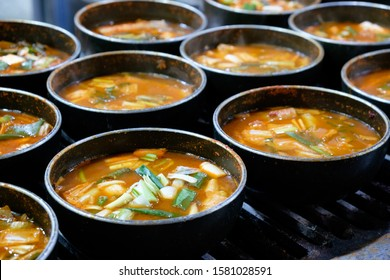 Steaming, sizzling and boiling black pots on gas stove with orange asian street food from vegetables in a stall at namdaemun market, Seoul, South Korea