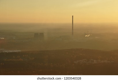 Steaming smoke stack and cooling tower with pollution. Chimney emission of fumes and steam in the air. Factory fumes