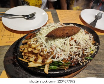 Steaming Veg sizzler of noodles and potato chips with lot of cheese and empty dishes and fork ready to serve