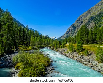 steaming water in the swiss alp valley of val roseg with typical glacier ice coloured water, deep green forests and grassland below blue sky near pontresina, st. moritz
