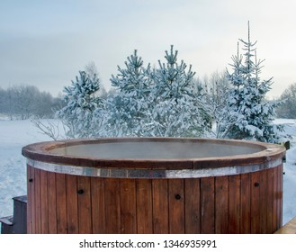 Steaming wooden hot tub with spa in winder with  snow and frosty Christmas trees in background - Image