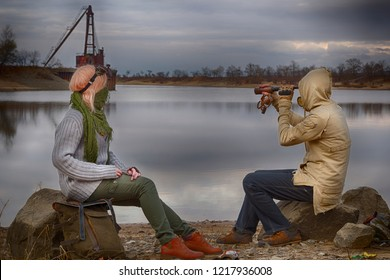 Steampunk adventurers couple: man and woman sitting on stones on river coast, man in hood looks in vintage telescope. Woman wearing goggles on head and neckerchief half mask