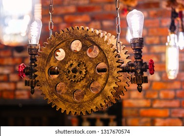 Steampunk architectural style design element of interior. Lamp bulbs fixed on iron industrial gear cogwheels sprocket lighting illuminated equipment hanging indoors