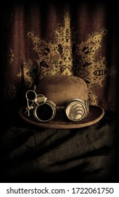 A Steampunk bowler hat with goggles containing a reflection of a hand