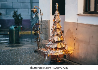 Steampunk christmas tree. Creative Steampunk steel tree with metal ornaments and branches, stylish christmas decorations and garland lights in european city street. Festive decor