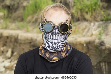 Steampunk or cyberpunk or anonymous hacker portrait of man in goggles and half-face bandit skull mask (bandana buff scarf)