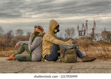 Steampunk or cyberpunk style adventurers couple, woman in goggles and neckerchief half face mask, man in hood and respirator gas mask, rest on the ground leaning back against each other.