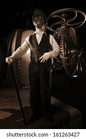 Steampunk figure in top hat and gas mask stands near huge gears and valves