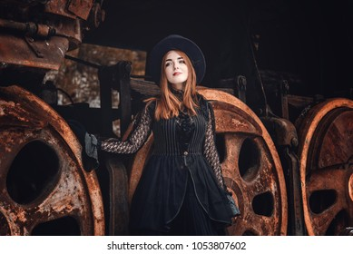 Steampunk girl in black dress and hat near old steam locomotive and big iron wheels. Red-haired beauty . Vintage portrait of the last century, a retro trip
