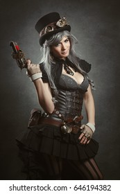 Steampunk girl posing with mechanical firearm. Texturized background