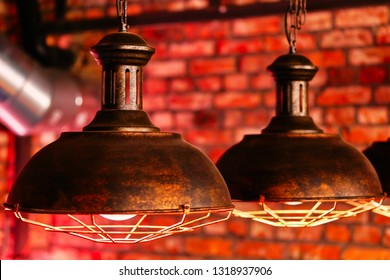 Steampunk style design element lamps hanging view over red brick wall close up