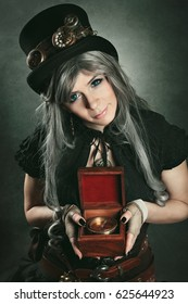 Steampunk traveller with old wooden compass in hand