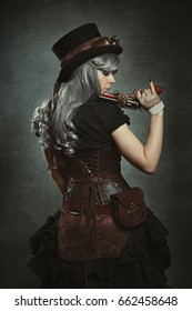 Steampunk woman with mechanical gun. Beautiful dress